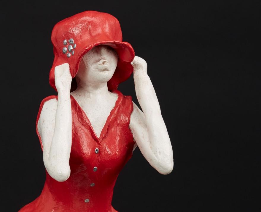 Sculpture en métal et argile représentant une femme à la robe rouge qui a râté son train et enfonce son chapeau de dépit
